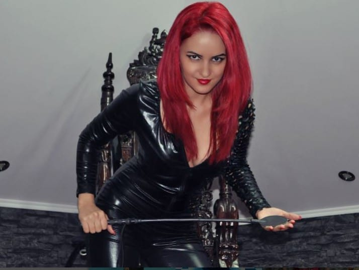 sexy domme wearing tight black pvc catsuit holding a whip on cam